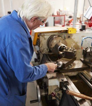 senior-engineer-operating-industrial-machinery-in-PLGWEUZ-683x1024
